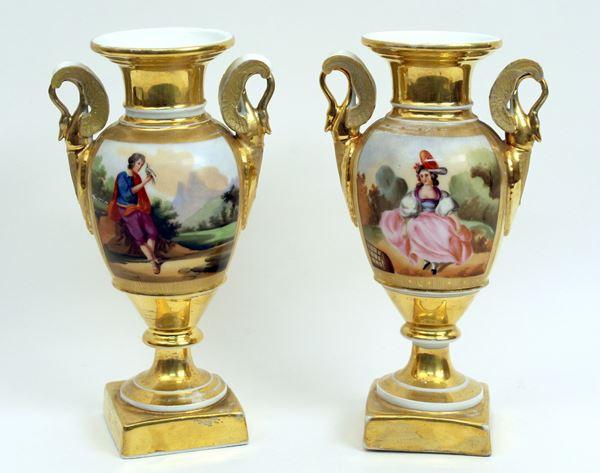 Coppia di vasetti in porcellana dorata con riserve raffiguranti paesaggi e figure, anse a cigni, H 20 cm.