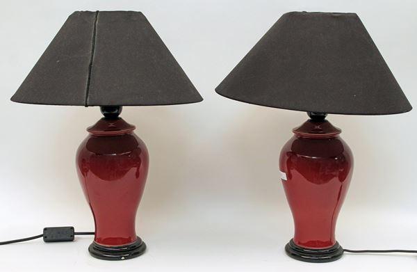 Coppia di lampade in maiolica bordeaux, XX sec., H 44 cm.