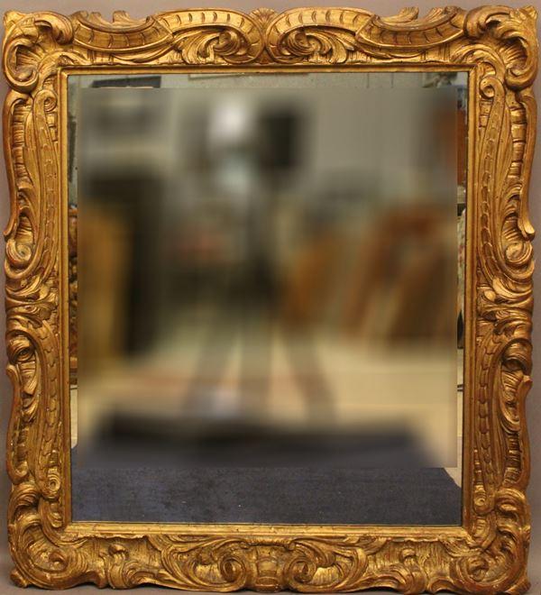 Specchiera di linea rettangolare in legno intagliato e dorato, 100x90 cm.