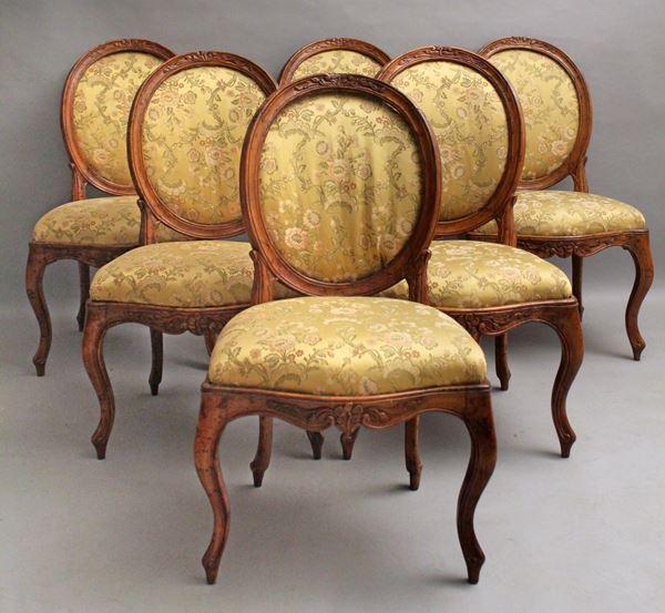 Lotto composto da sei sedie Luigi XV in noce, particolari intagliati, con dorsale a medaglione e rivestite in stoffa fiorata.