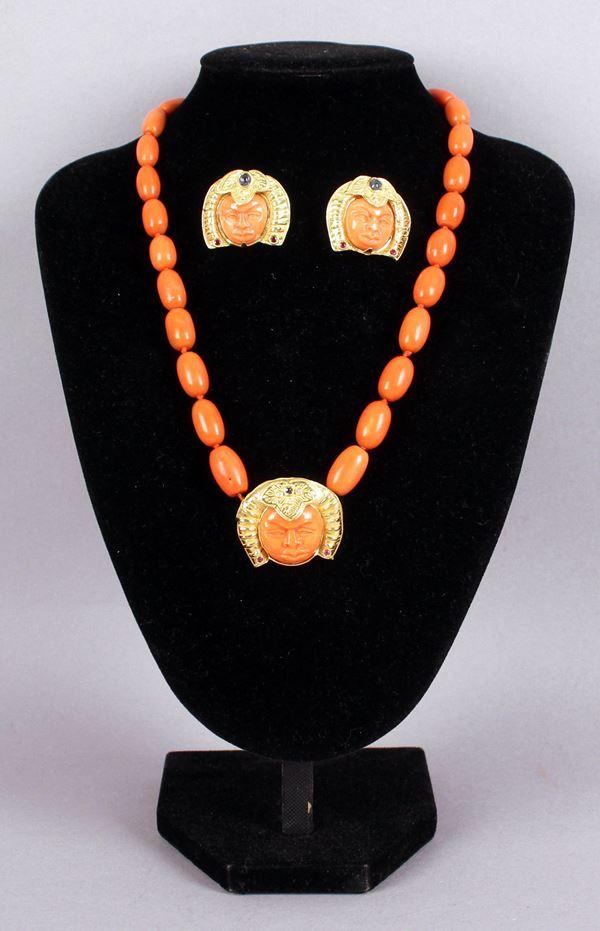 Parure in corallo con pendente e orecchii a forma di volto di Budda, con finiture in oro 18 Kt, applicazioni in pietre pregiate, zaffiri, rubini e brillantini, gr. Tot. 98,2.