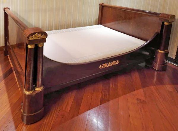 Letto Impero a barca in mogano e piuma con laterali a colonnine, finiture in bronzo dorato e cesellato, altezza 107x212x138 cm.
