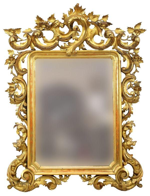 Specchiera in legno intagliato e dorato a motivi di foglie d'acanto, fiori e teste zoomorfe, altezza 192x140 cm, XIX secolo, (difetti).