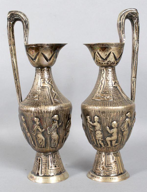 Coppia di caraffe in argento sbalzato ed inciso raffiguranti figure, altezza 26,5 cm, gr. 760.