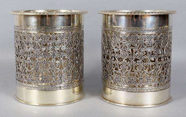 Coppia di portabottiglie in argento traforato e cesellato, altezza 13,5 cm, diametro 12 cm, gr. 750.