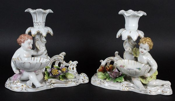 Coppia di candelieri in porcellana policroma con salierine sorrette da putti, cm 17x18x14, Dresda, XIX secolo, marcati sotto la base, (lievi sbeccature)
