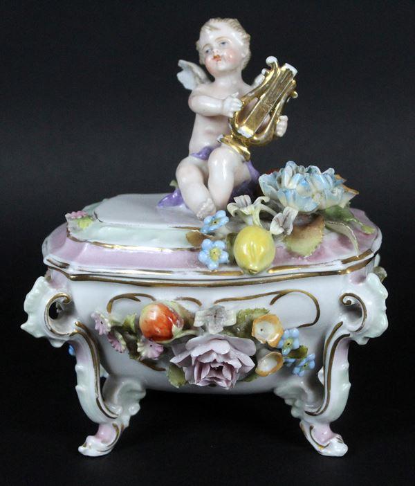Cofanetto in porcellana policroma, coperchio sormontato da putto musicante, altezza 16 cm (lievi difetti)