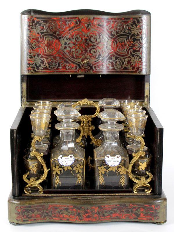 Cave a Liqueur, intarsiato alla maniera Boulle in tartaruga e bronzo, completo di 4 bottiglie e 15 bicchierini in cristallo decorata in oro, altezza cm 26,5x34x26, XIX secolo (mancante un bicchierino)