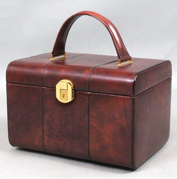 Beauty case in pelle bordeaux, chiusura in metallo dorato, con all'interno specchio ed un taschino, cm. 18x28x21.