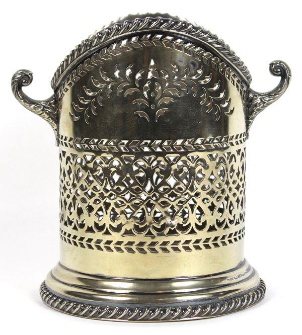 Porta bottiglia in metallo argentato e traforato, bordi lavorati, due prese laterali a volute, altezza cm. 18, diametro cm. 14, marca e punzoni sotto la base.