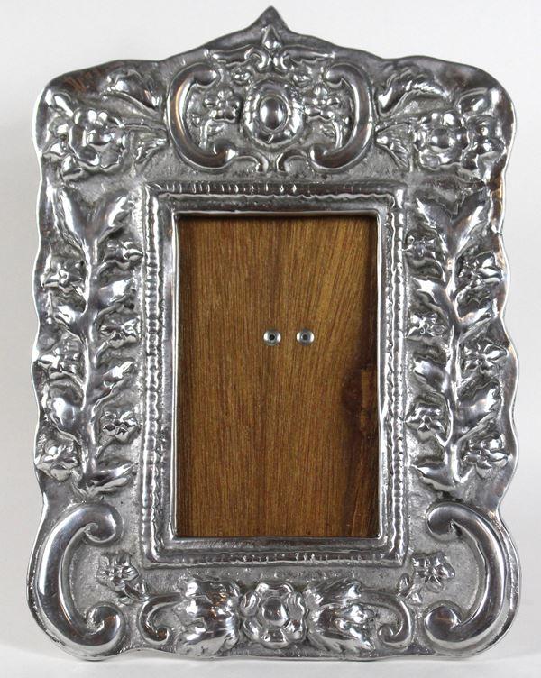 Cornice portafoto in metallo argentato, decoro a rilievo a motivi vegetali e volute, cm. 29x22.