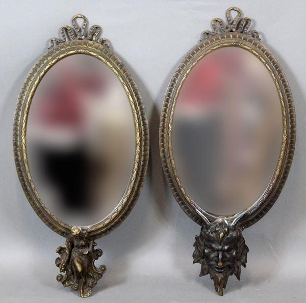 Coppia di specchiere di linea ovale, in metallo brunito con finali raffiguranti testa di satiro e figura allegorica con clessidra e cornucopia, cm 64x32, inizi XX secolo.