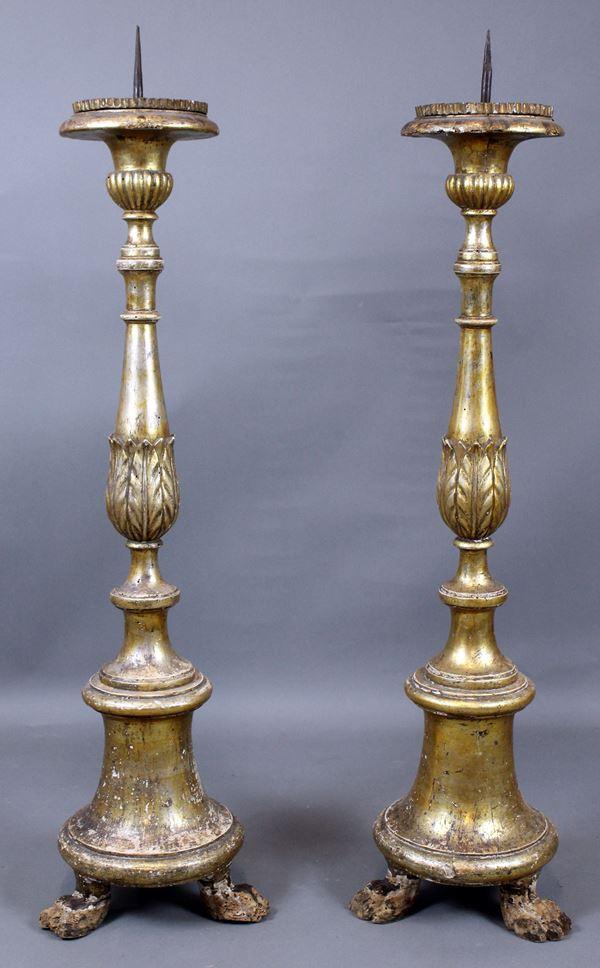 Coppia di torcieri in legno intagliato e dorato, poggianti su tre piedi ferini, altezza cm. 101, XIX secolo, (difetti e mancanze).