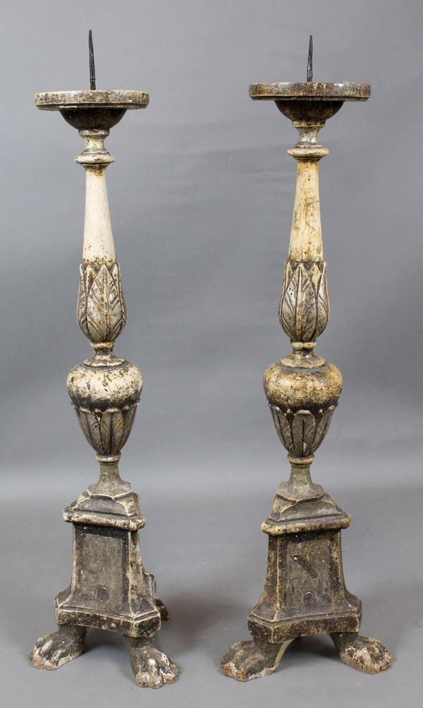 Coppia di torcieri in legno intagliato e laccato, altezza cm. 85, poggianti su piedi ferini, XIX secolo, (difetti).