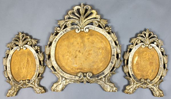 Tre cartaglorie del XVIII secolo, in legno intagliato e dorato, cm. 48x40, decori a volute e fiori, piedi a zampa ferina.