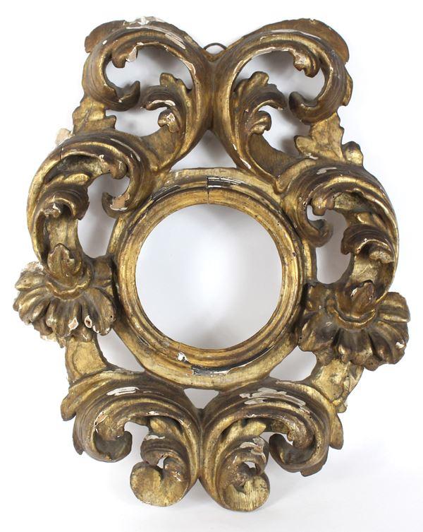 Cornice bolognose del XVII secolo, in legno dorato ed intagliato a volute di foglie d'acanto, ingombro cm. 58x45, diametro luce cm.17, (difetti).