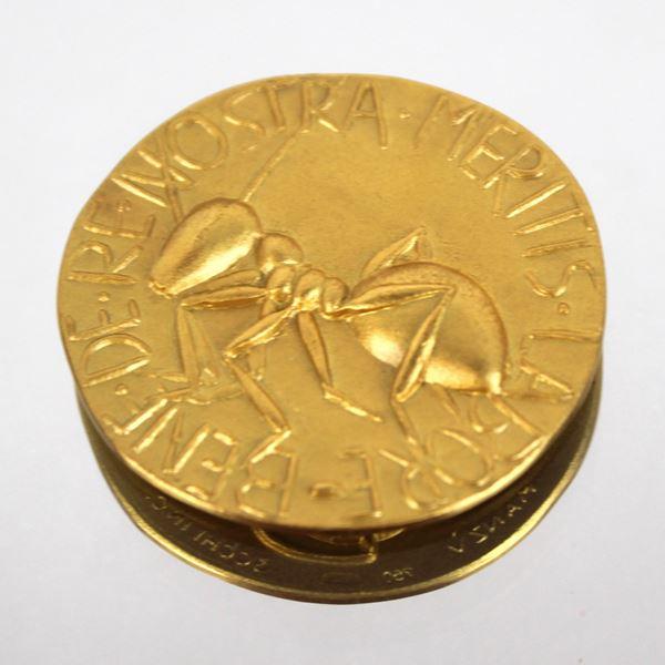 """Medaglia in oro 18 kt raffigurante formica con iscrizione """"Bene de re nostra meritis labore"""" disegnata da Giacomo Manzù (1908-1991), incisore Giuseppe Trecchi, diametro cm. 3,5, gr. 26,1"""