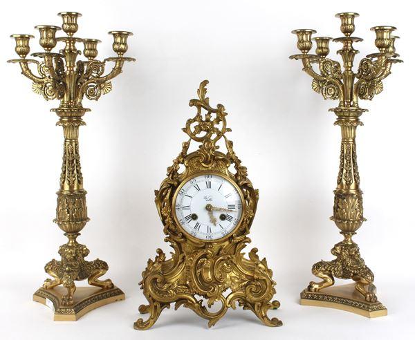 Orologio da tavolo e coppia di candelabri in bronzo dorato